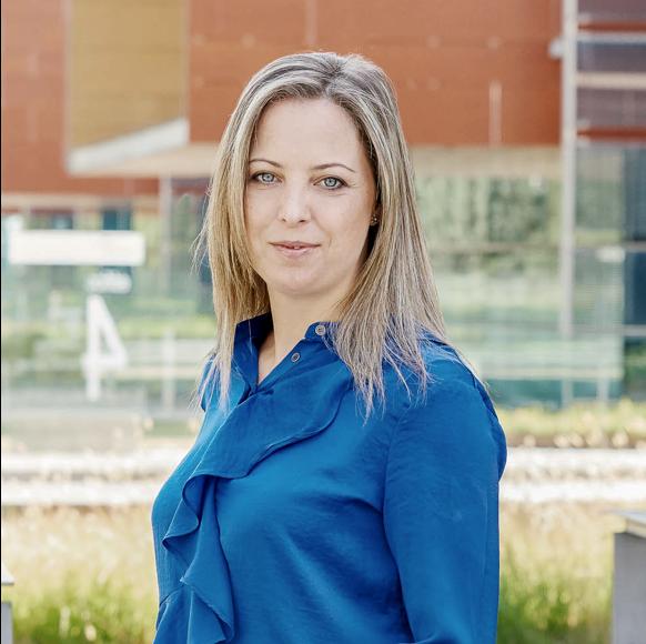 Carmen Cantero, Regional Program Manager on a blue top standing outside Mindcurv S.L. office in Alcobendas, Spain