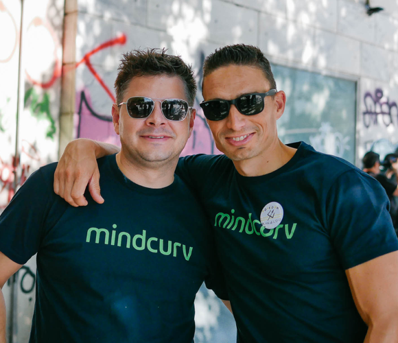 Man with arm around another one wearing sunglasses and Mindcurv tshirts at Mindcurv's Curv 360 celebration event in Athens