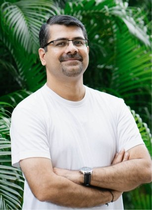 Mohan Gopinath, Delivery Vice President standing in front of palm trees at the World Trade Center Kochi