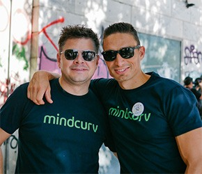 Two Mindcurv members wearing sunglasses and Mindcurv tshirts at Mindcurv's Curv 360 celebration event in Athens
