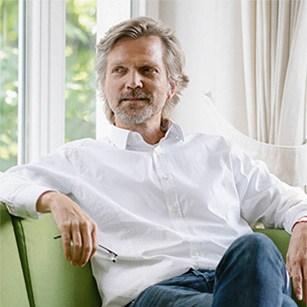 Vincent De Jong, Director sitting on green sofa, holding reading glasses at Mindcurv Essen office