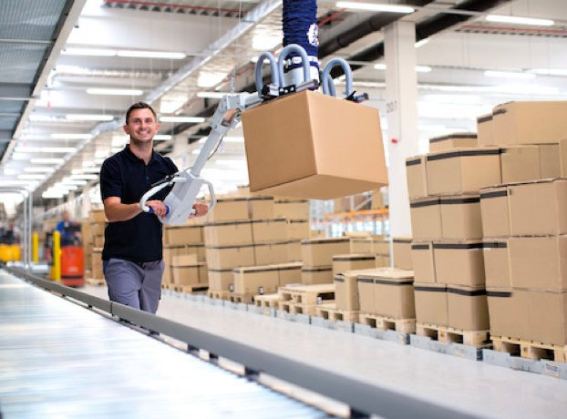 man at Schmalz factory using a robot to move boxes